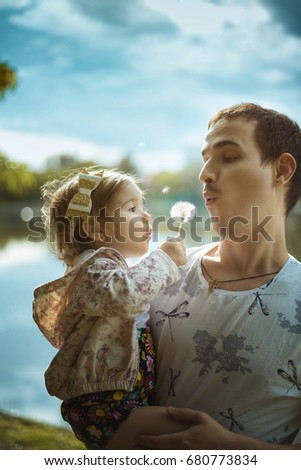 Young father holding his little daughter in hands and helping her to to blow away dandelion