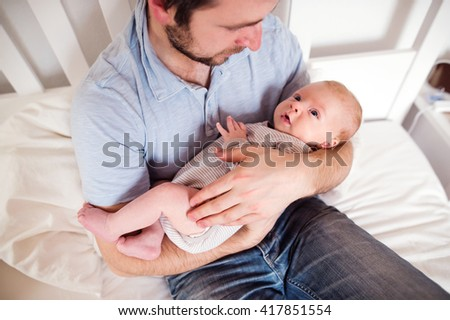Young father holding his newborn baby son, home bedroom