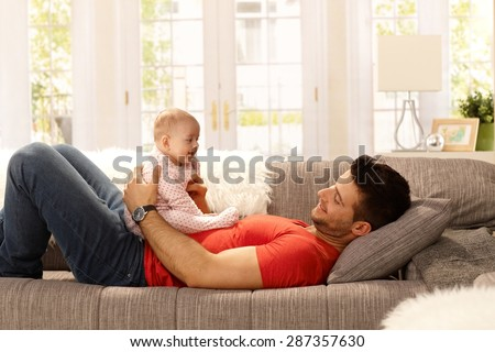 Young father holding little daughter on his belly as lying on sofa, playing. Side view. - stock photo