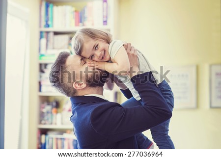 Young father hugging his daughter as he gets home from work - stock photo