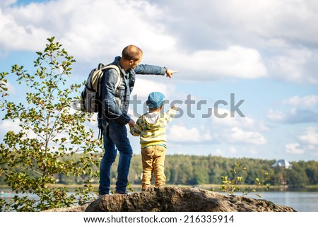 Young father is hiking with 3 year old son  - stock photo