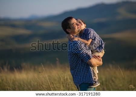 Young father is holding his son on hands in the summer - stock photo