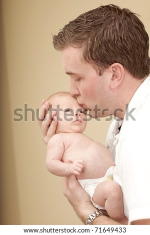 Young father kisses his newborn son