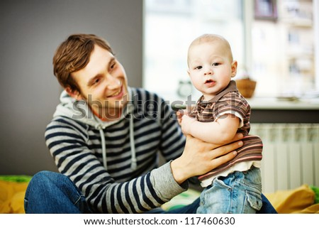 Young father lifting his baby and looking at him - stock photo