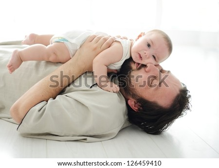Young father lying on floor at home and playing with adorable baby - stock photo