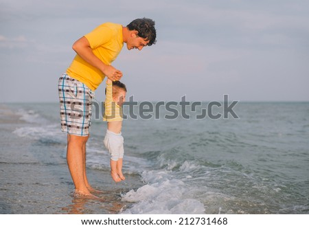 young father playing with his baby at the sea beach - stock photo