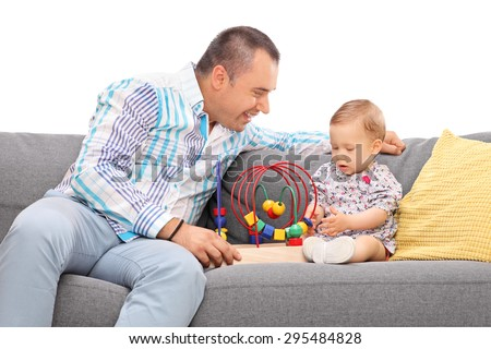 Young father playing with his baby daughter seated on a gray couch isolated on white background - stock photo