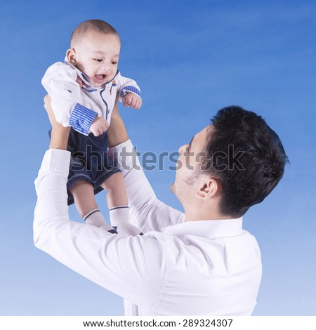 Young father playing with his baby outside and lift up the baby under blue sky