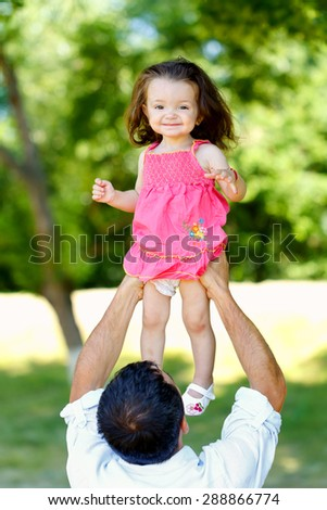 Young father playing with his beautiful daughter - stock photo
