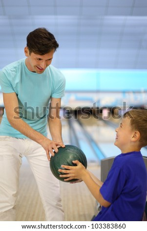 Young father plays with son in bowling club; focus on ball; shallow depth of field - stock photo