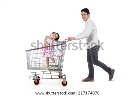 Young father pushing a shopping cart with his daughter inside it, isolated over white - stock photo