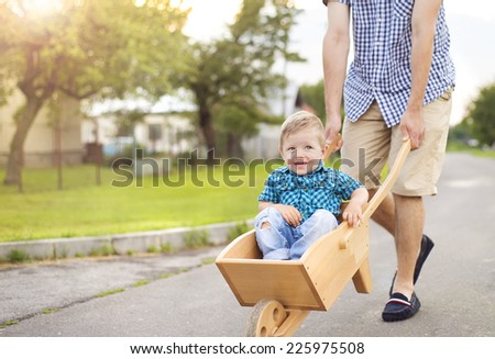 Young father pushing his little son in wooden wheelbarrow on road on sunny day - stock photo