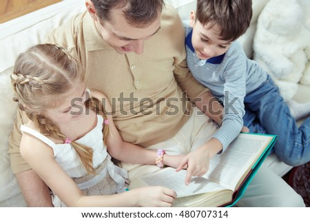 Young father reading fairy tale with his two children