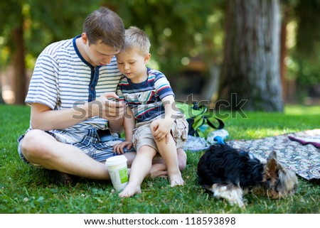 Young father reading to his son outdoors - stock photo
