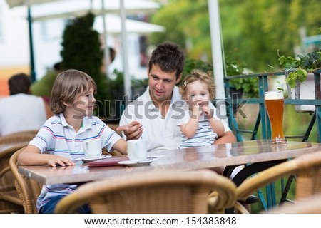 Young father relaxing in an outside cafe with his children, a school boy and cute curly baby girl having a drink together on a nice warm summer day - stock photo