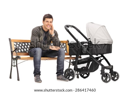 Young father sitting on a wooden bench with a baby stroller beside him isolated on white background - stock photo