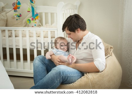 Young father sitting with his baby son on hands at bedroom - stock photo