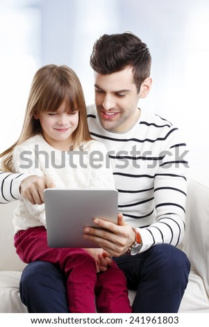 Young father studying his little daughter how to use internet safety at home.