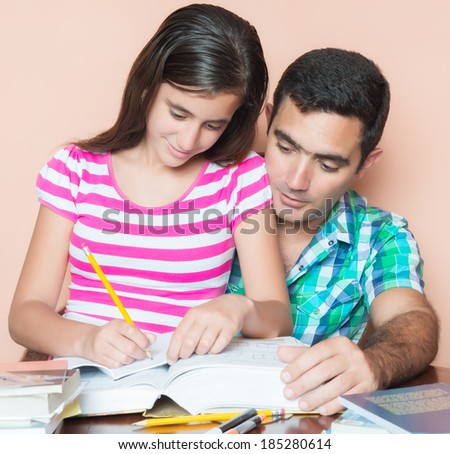 Young father studying with his teenage daughter at home - stock photo
