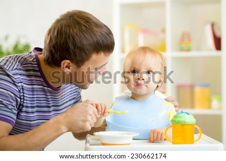 young father teaching baby kid son to eat with spoon
