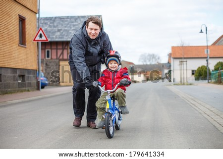 Young father teaching his 3 years old little son to ride a bike, outdoors - stock photo