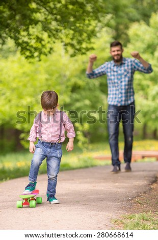 Young father teaching son to ride skate in summer park. - stock photo
