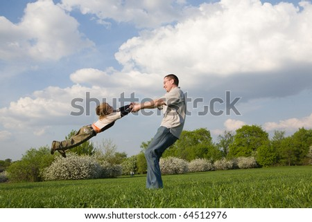 Young father twirling his little son in park