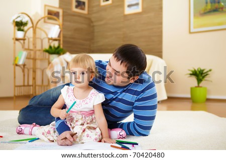 young father with a daughter at home in the living-room