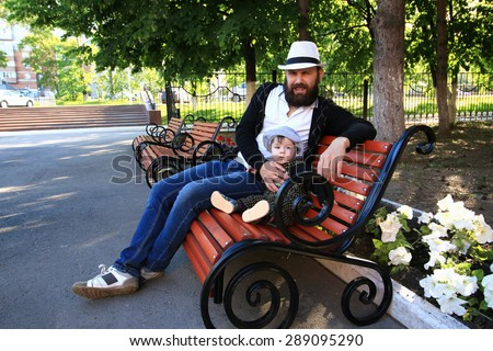 young father with children resting on a bench