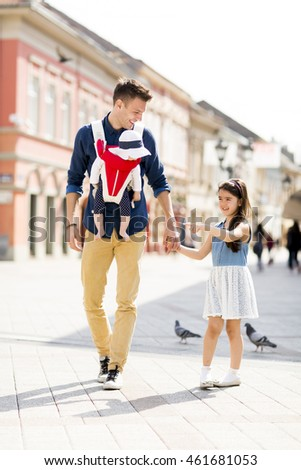 Young father with cute daughters on the street