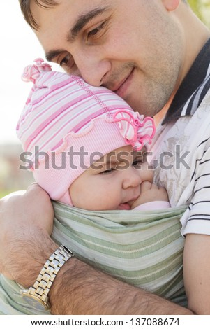 Young father with his daughter in sling, spring outdoor - stock photo