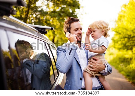Young father with his little boy and smartphone at the car.