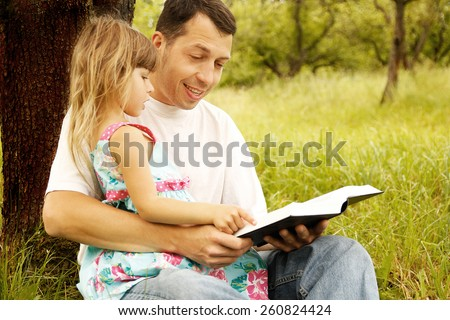 young father with his little daughter reads the Bible - stock photo