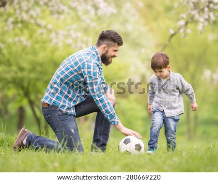 Young father with his little son having fun on football pitch. - stock photo