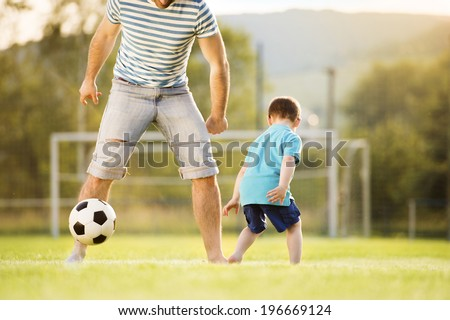 Young father with his little son playing football on football pitch - stock photo