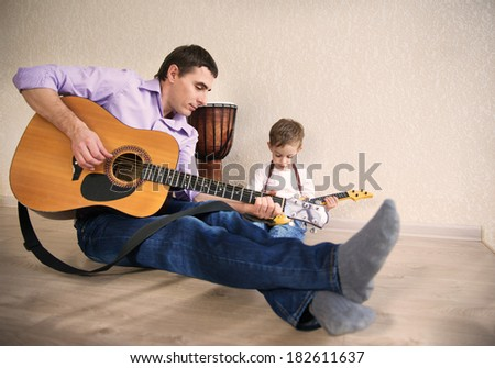 Young father with his little son playing guitar