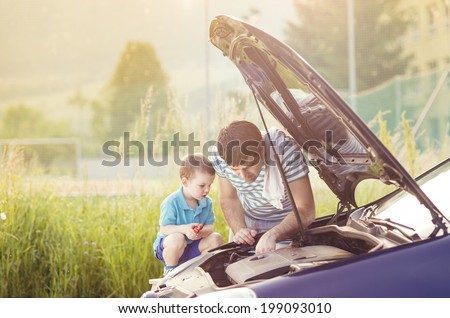 Young father with his little son repairing car - stock photo