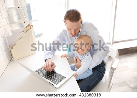 Young father with his little son working at home - stock photo