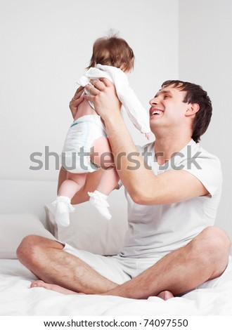 young father with his six months old daughter on the bed at home