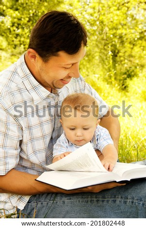 Young father with his son reading the Bible