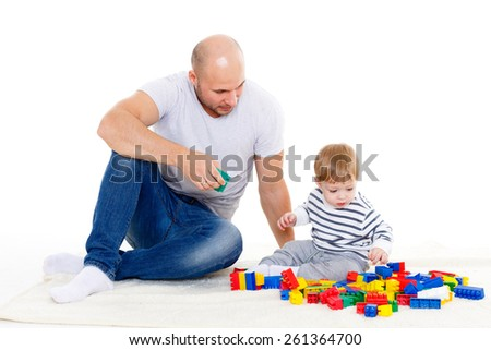 Young father with small baby play on a white background. Early development and educational toys. Happy family.