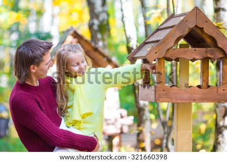 Young father witk little daughter in autumn park outdoors