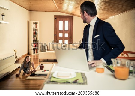 Young father working at home during breakfast while his little girl is playing on the floor