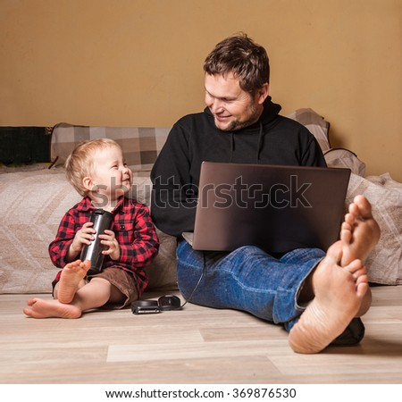 Young father working at home with computer and his child