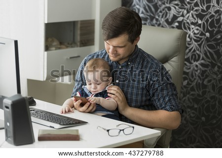 Young father working from home and taking care of his baby son