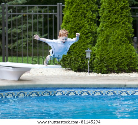 Young fearless boy jumping into swimming pool