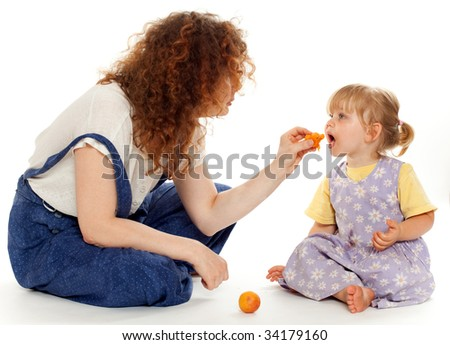 young feeding small young girl fruit woman