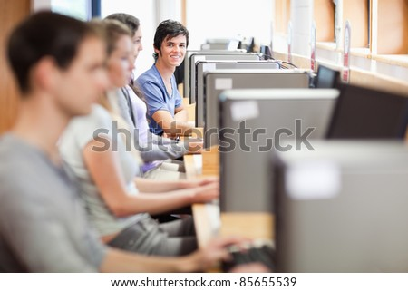 Young fellow students in an IT room with the camera focus on the background - stock photo