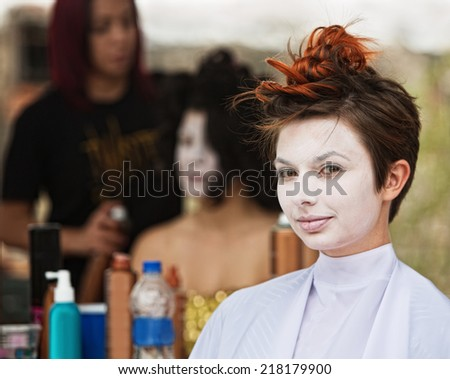Young female actress in white make up sitting - stock photo