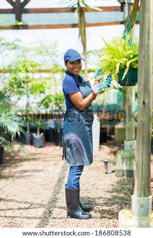 young female african gardener working in greenhouse - stock photo